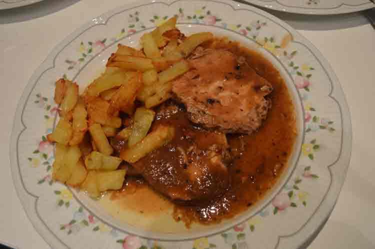 Redondo de lomo de cerdo en salsa de cebolla con patatas fritas