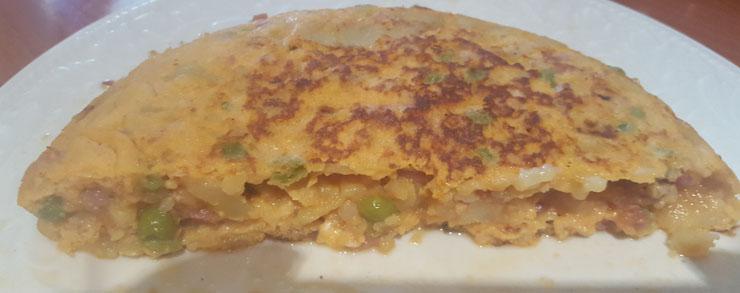 corte tortilla de patata cebolla jamon y guisantes