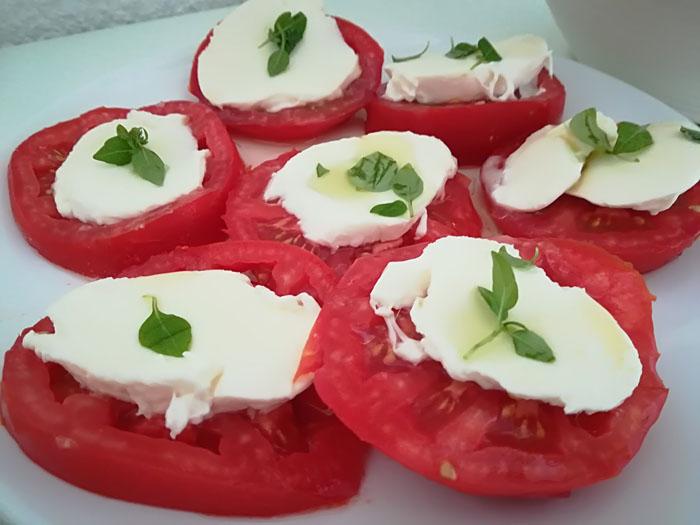 rodajas de tomate, queso mozzarela y hojas de albahaca