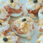 Huevos rellenos decorados con mayonesa, yema y alcaparras